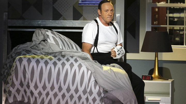 Kevin Spacey sits on a bed on stage at the Tony awards.