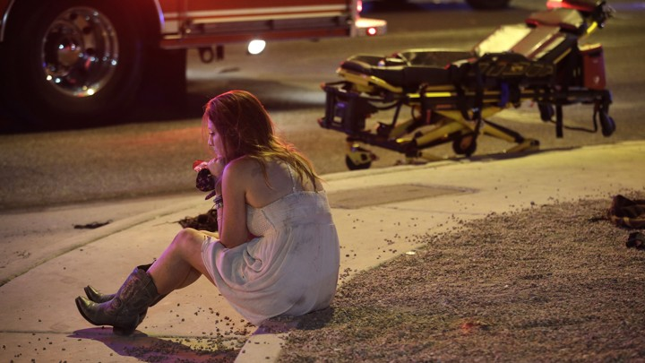 A young woman sits on a curb in Las Vegas, with an EMS vehicle behind her