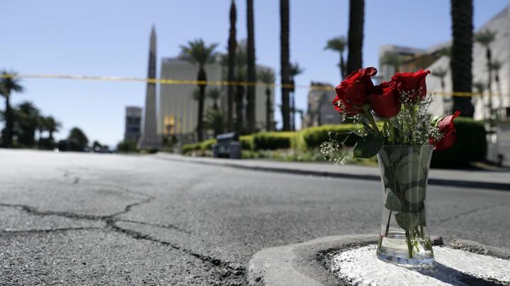 A vase of roses on a sidewalk