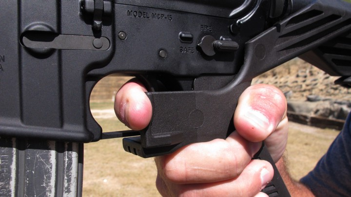 "A shooting instructor illustrates the grip on an AR-15 rifle fitted with a ""bump stock"" at a gun club."
