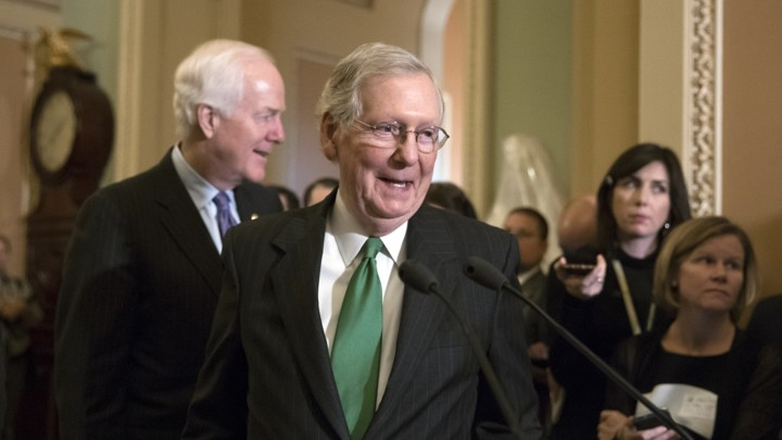 Senate Majority Leader Mitch McConnell steps up to a microphone.
