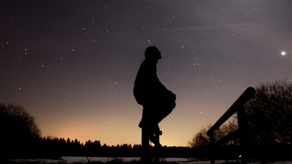 A person in silhouette against a starry sky