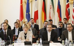 EU and Iranian delegates sitting at a table with flags behind them.