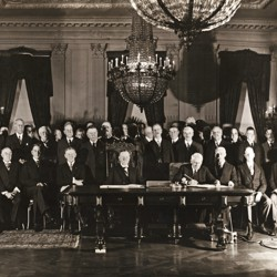 Members of the Cabinet, Senate, and Congress are seen gathered in the East Room of the White House, after President Coolidge and Secretary of State Kellogg signed the Kellogg-Briand Pact.