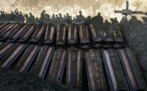 Shadows of people burying dozens of coffins in a mass grave.