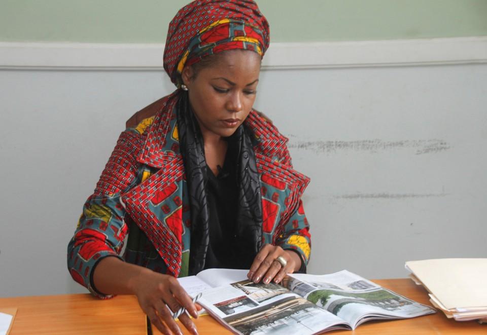 MacDella Cooper reads a magazine at her desk.