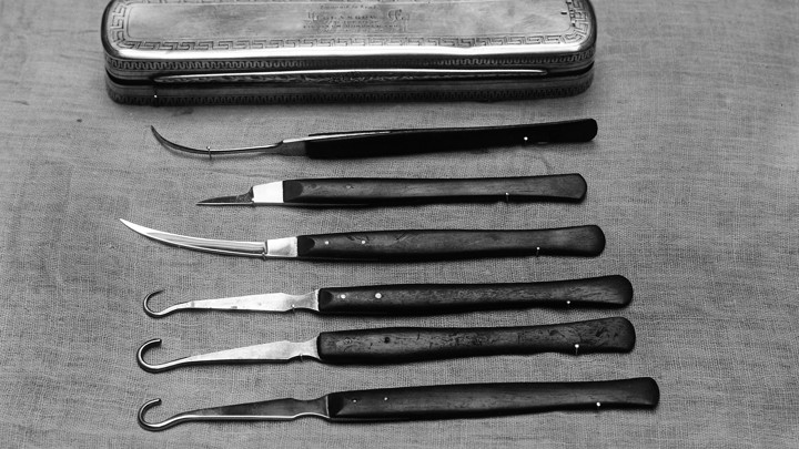 A set of silver and black surgical instruments and a silver case
