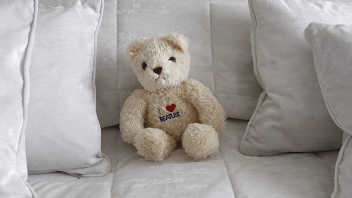 A teddy bear on a bed surrounded by pillows