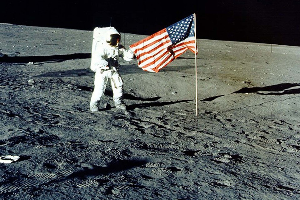 "Charles ""Pete"" Conrad Jr. stands with the U.S. flag on the lunar surface during the Apollo 12 mission in 1969."
