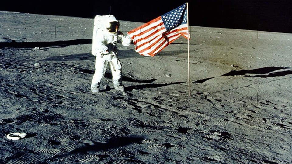 """Charles """"Pete"""" Conrad Jr. stands with the U.S. flag on the lunar surface during the Apollo 12 mission in 1969."""