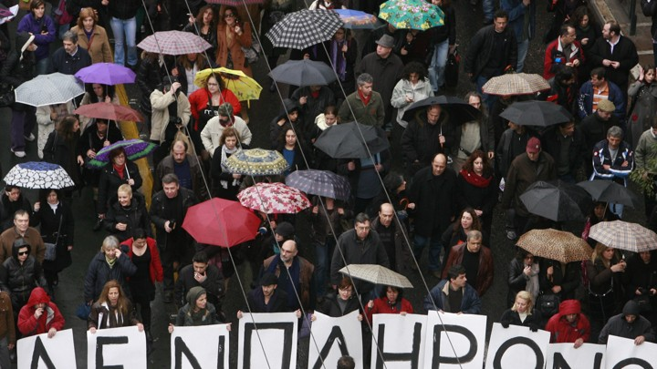 Protesters march under umbrellas during an anti-government rally
