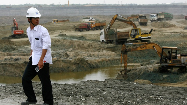 A Chinese engineer watches excavation work at the construction site for the Hambantota port.