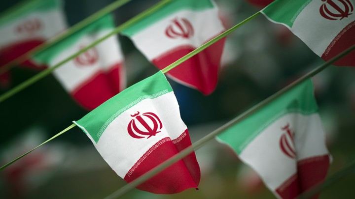 Iran's national flags are seen fluttering on a string in a square.