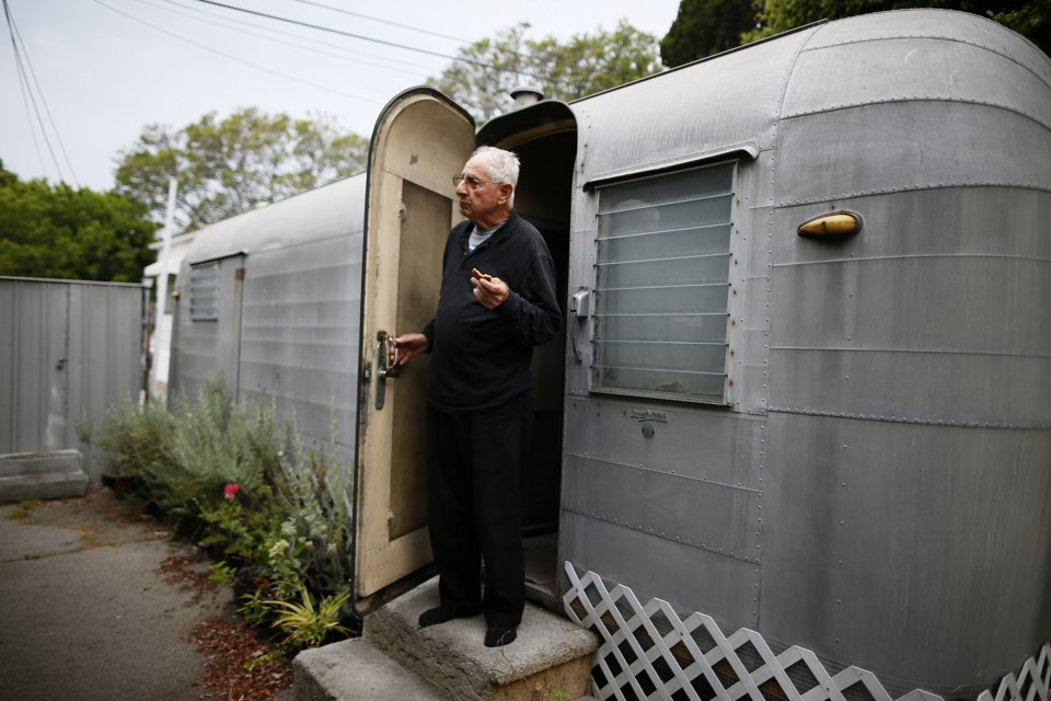 A man standing in the doorway of his mobile home