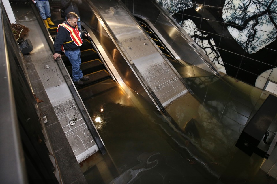 A man in a construction vest stands on a flooded escalator in a subway station.