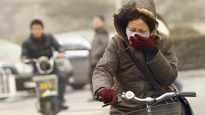 A woman covers her face while riding her bike.