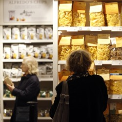 Shoppers select products and take pictures on their smartphones at an Eataly store.