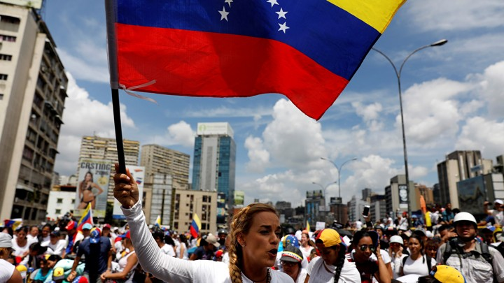 Lilian Tintori waves a Venezuelan flag amid a group of female protesters.