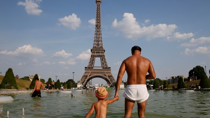 A man and a young child with sunburned bodies stand in a pool of water in front of the Eiffel Tower.