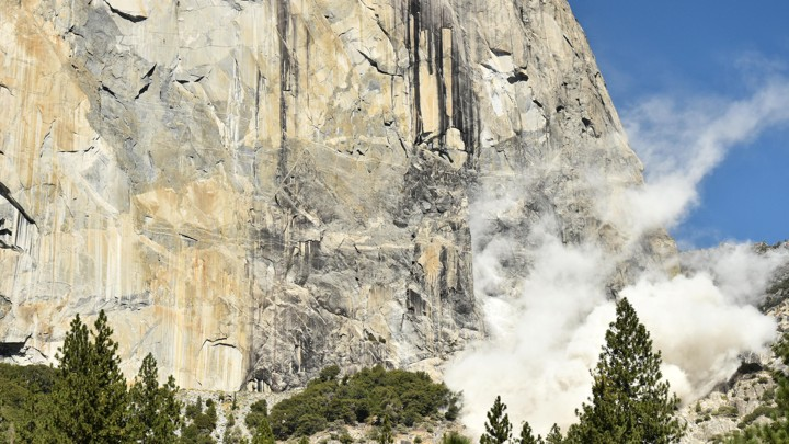 The face of El Capitan with dust rising from the ground