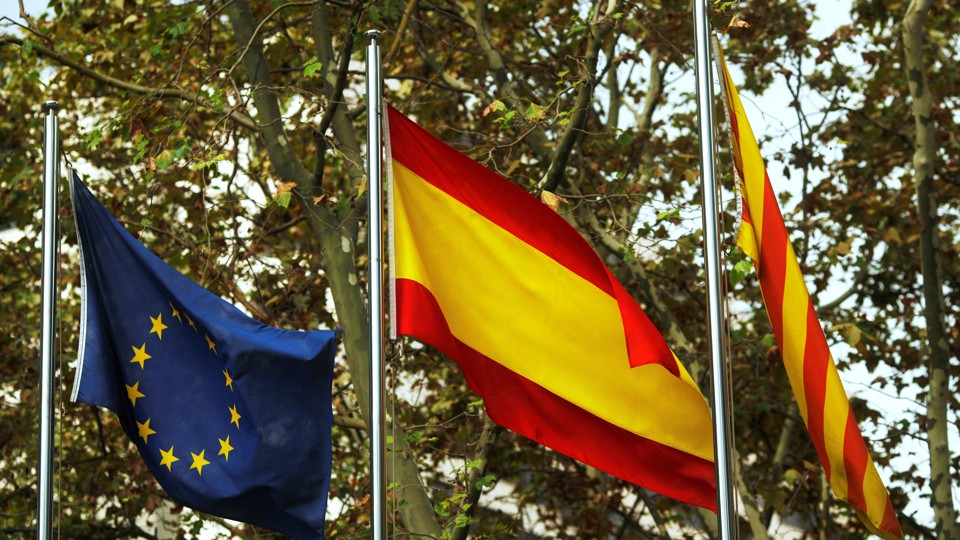 European Union, Spanish, and Catalan flags are seen.