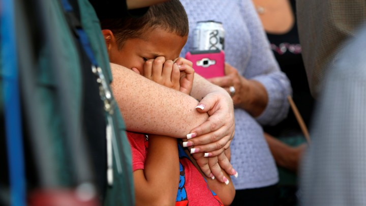 A young boy cries in a woman's embrace at a prayer vigil following the mass shooting in Las Vegas.