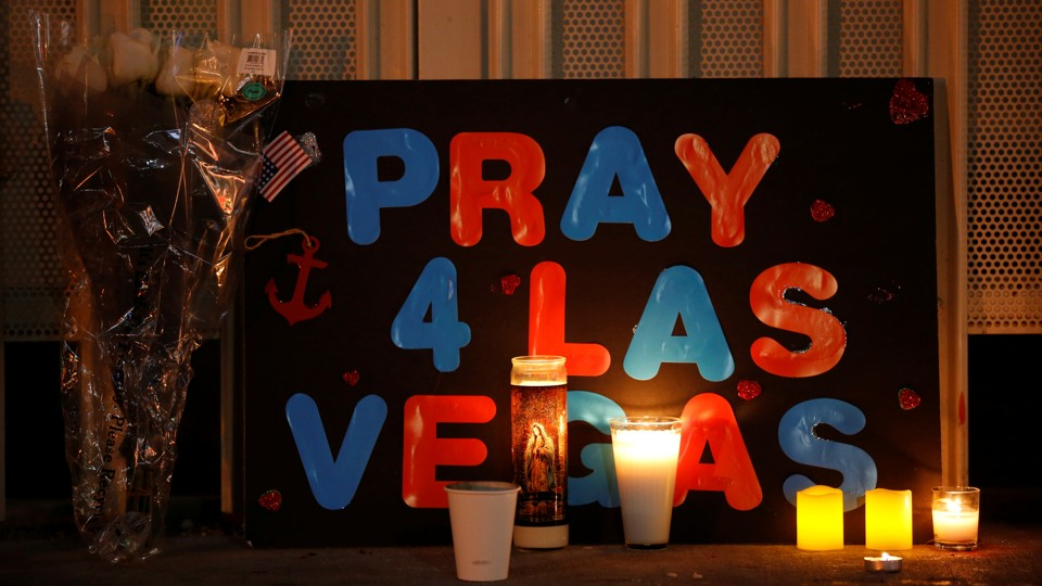 """A poster next to flowers and candles reads, """"Pray 4 Las Vegas"""""""