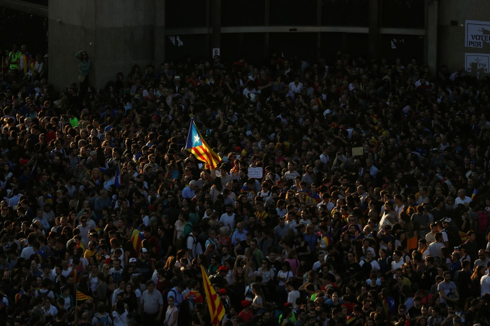 A Catalan separatist flag flutters in the middle of a crowd.