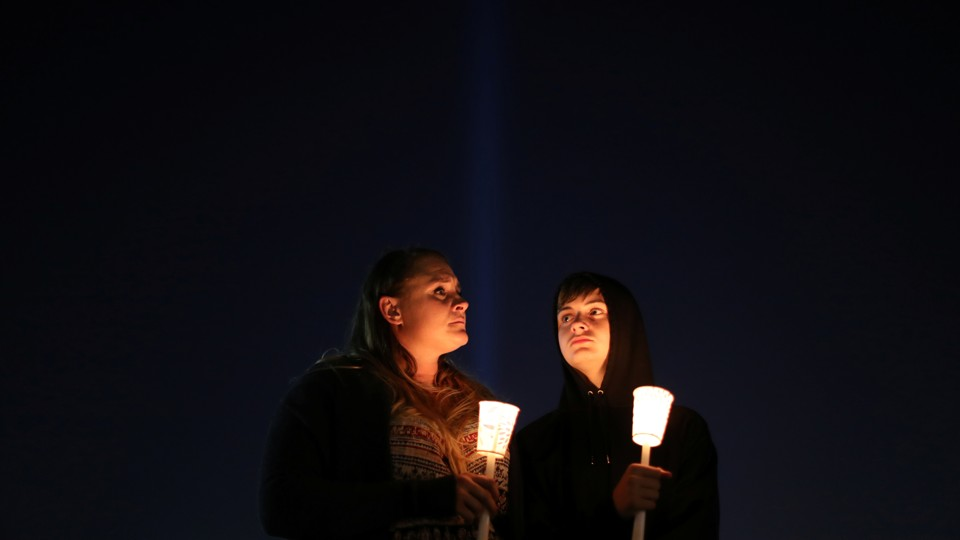 People hold candles at a vigil.