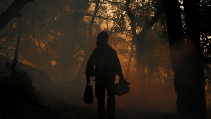 A firefighter walks through a dark, smoky forest