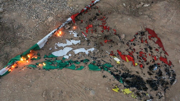 A burnt Kurdistan flag lying in the dirt.
