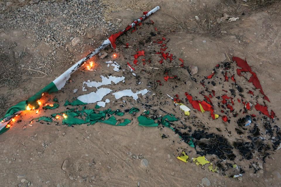A burnt Kurdistan flag lying in the dirt.