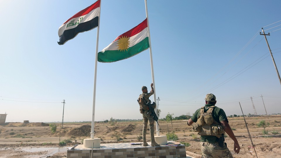 An Iraqi soldier takes down a Kurdish flag in Kirkuk