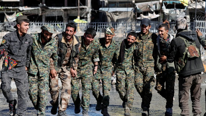 Fighters of the Syrian Democratic Forces dance along a street.