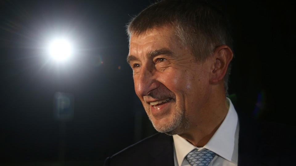 Andrej Babis against a black background with a light shining on him.