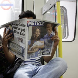 People read newspapers on the London Tube.