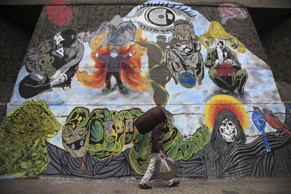 A worker walks past graffiti denouncing the Interior Ministry and the Egyptian uprising.