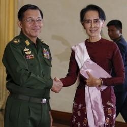 Senior General Min Aung Hlaing shakes hands with Aung San Suu Kyi.