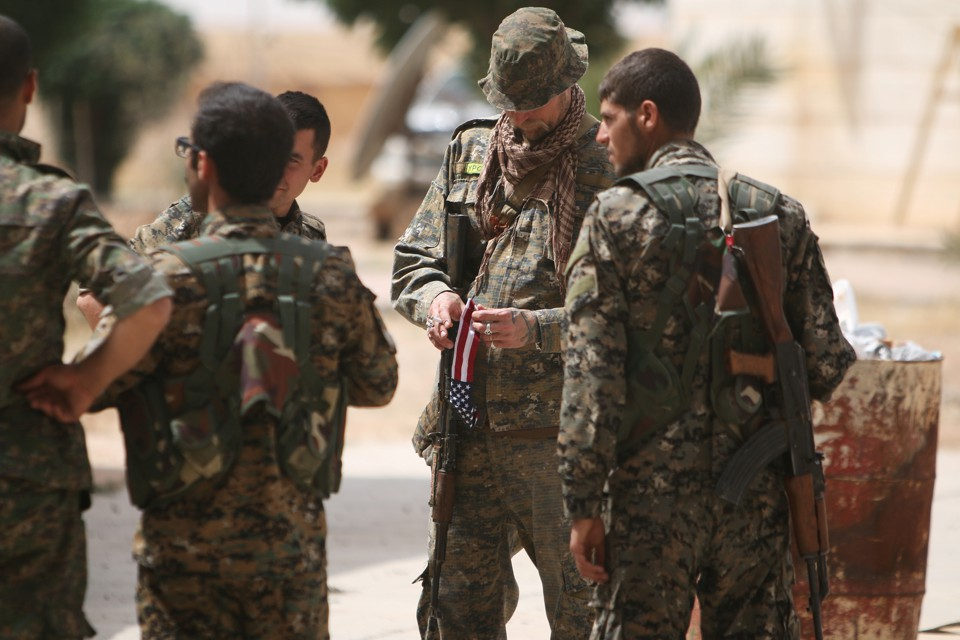 An American fighter carries the American flag as he stands with Syria Democratic Forces (SDF) fighters.