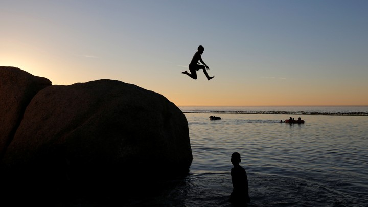 A child jumps off a rock into a body of water at sunset or sunrise