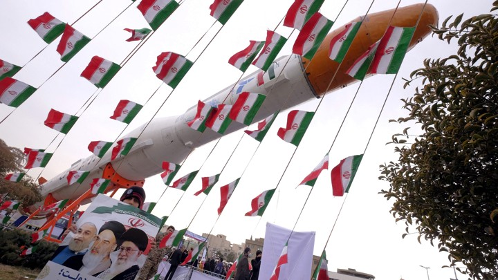 A boy holding a placard with pictures of President Hassan Rouhani, Ayatollah Ruhollah Khomeini, and Ayatollah Ali Khamenei, poses for camera in front of a model of Simorgh satellite-carrier rocket with Iranian flags everywhere.