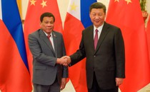 President Xi Jinping shakes hands with Philippines President Rodrigo Duterte in front of Chinese and Filipino flags.