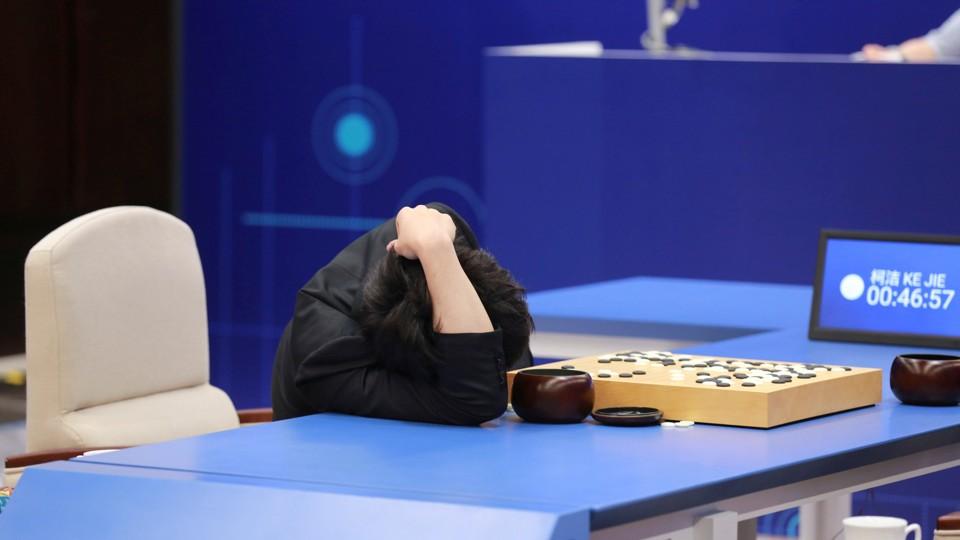 A man slumps in defeat over a Go board.