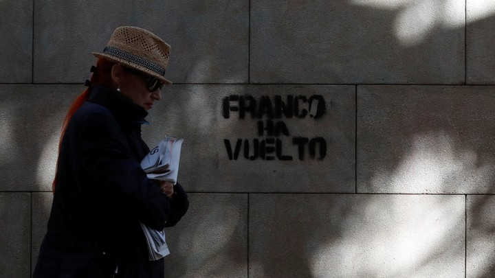 """A woman walks past a graffiti which reads """"Franco is back"""" in Barcelona, Spain on October 22, 2017."""