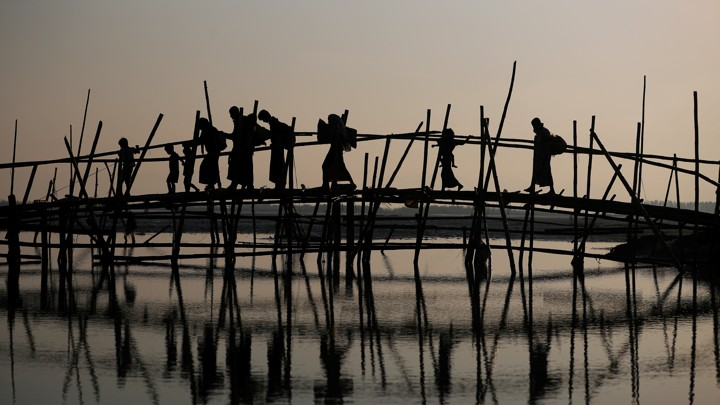 Rohingya refugees cross a bamboo bridge.
