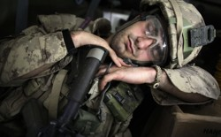 A soldier sleeping in uniform while leaning on his weapon