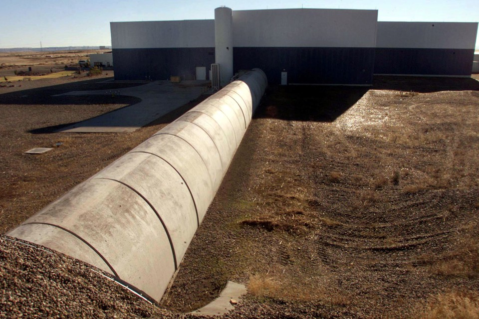 Concrete and steel tubes next to a plain building in a brown landscape