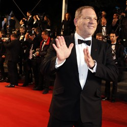 Harvey Weinstein poses on the red carpet with photographers behind him.