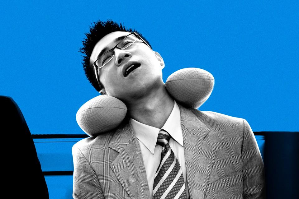 a businessman asleep on public transport using a neck pillow