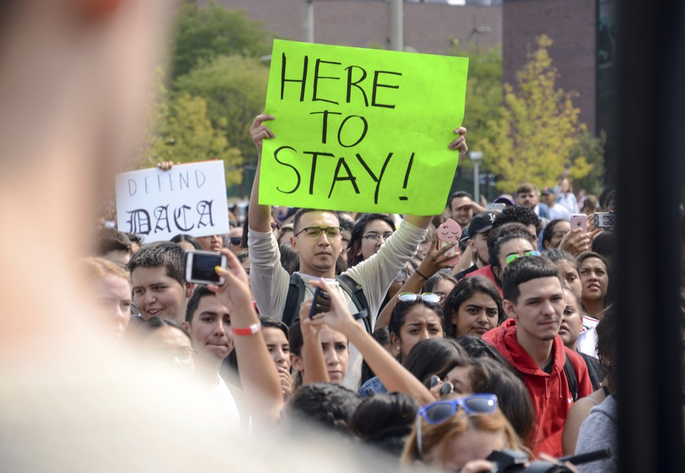 "A protester holds a sign that reads ""Here to Stay!"""